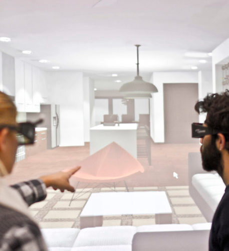 Two people, a female and a male, wearing virtual reality glasses. The virtual room is seen in their background.