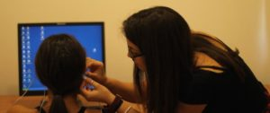A female researcher connecting an experiment's participant with an EEG.